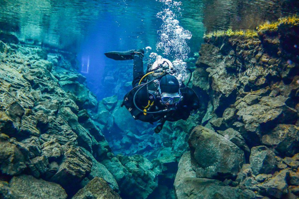 nurek eksploruje Silfrę szczelinę między płytami tektonicznymi w Parku Narodowym Thingvellir na Islandii